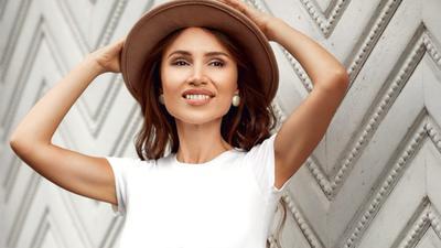 Junge Frau mit Hut an einer Wand
