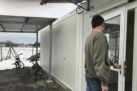 Mann öffnet Tür zur Wohnungslosenunterkunft in der Weingartener Dörnigstraße.