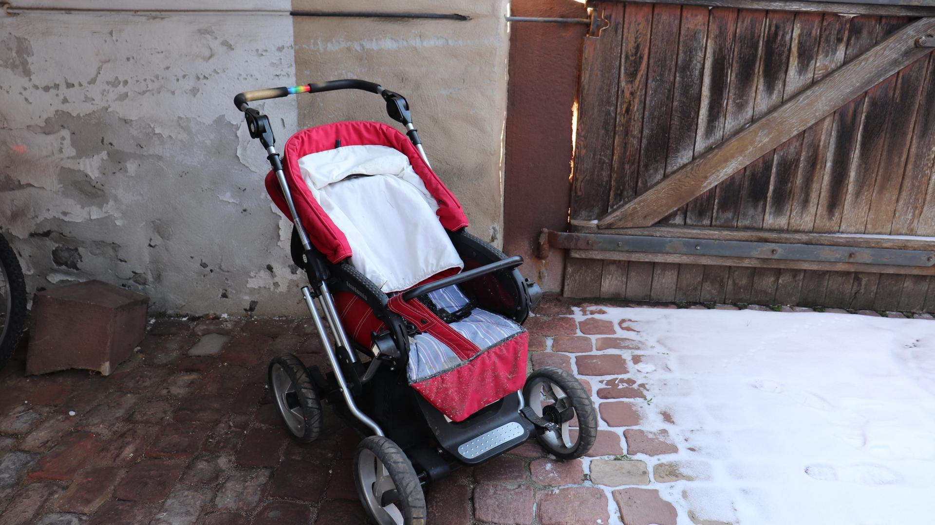Roter Kinderwagen in einem Innenhof