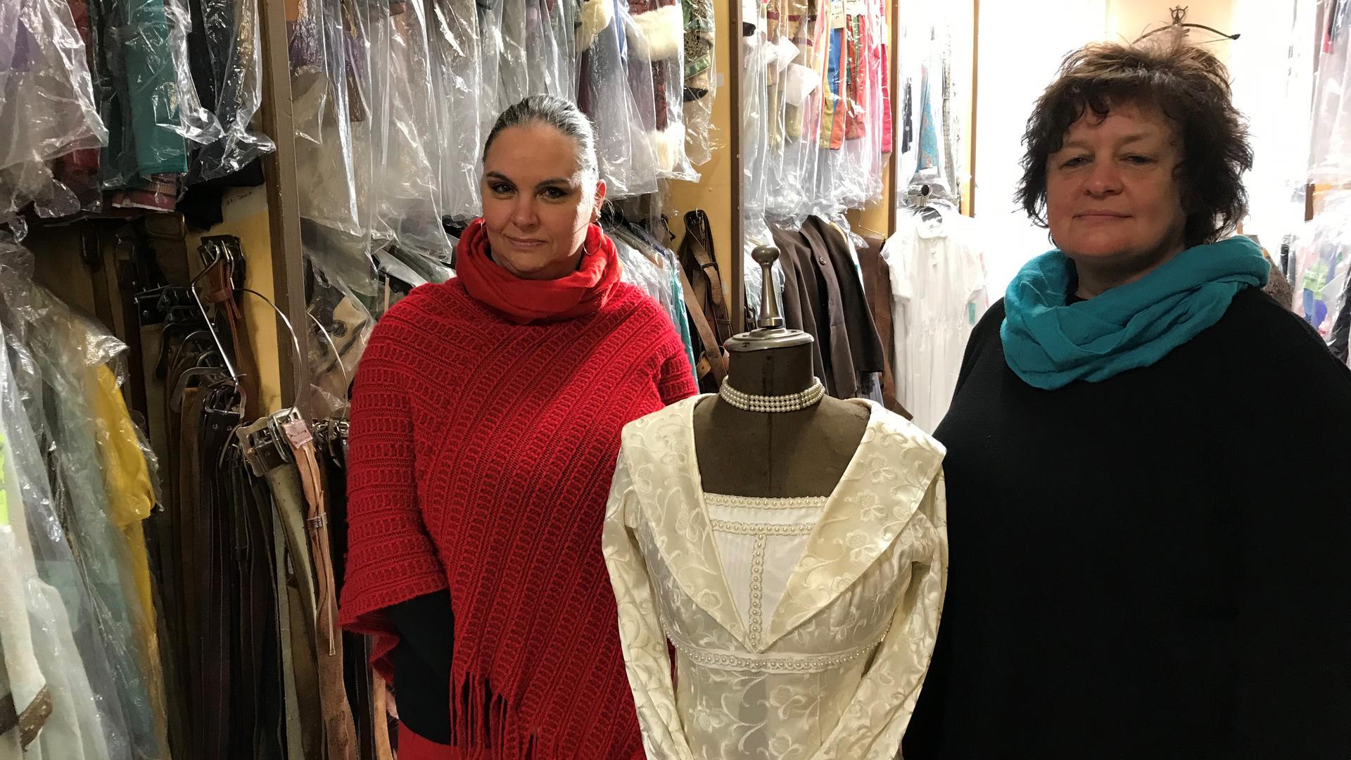 """Katharina Issel (l) und Andrea Reule im Kostümverleih """"Insignia Regis"""" in Dettenheim. In der Mitte ein weißes Kleid."""