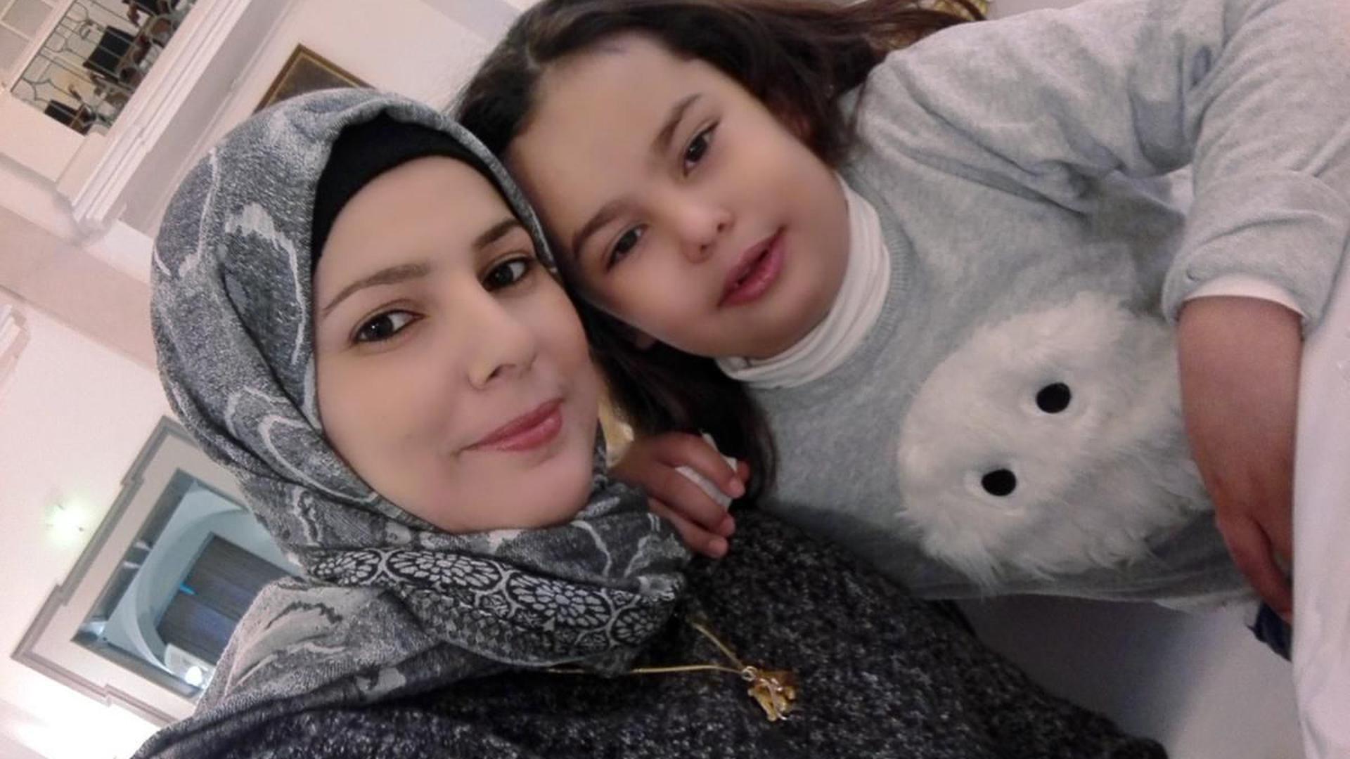 Mutter und Tochter in gedecktem Saal Köpfe aneinander geschmiegt, sitzend