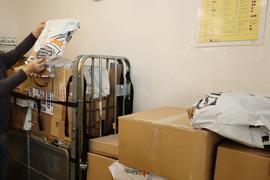 Mann in Postraum beim Paketesortieren