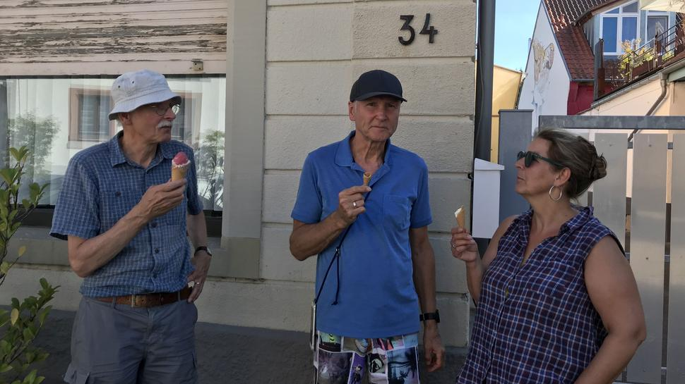 Drei Personen schlecken Eis.