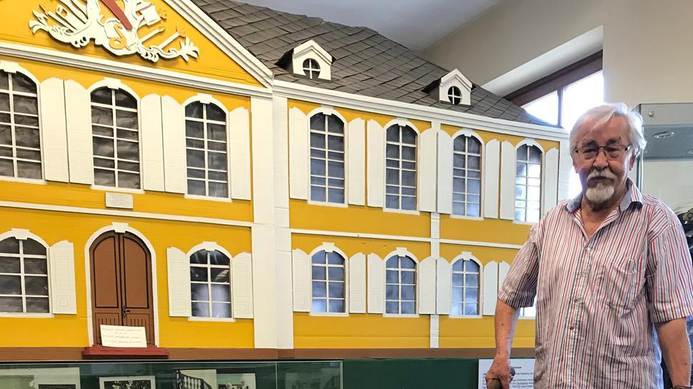 Ein Mann steht mit einem historischen Schubkarren im Museum.