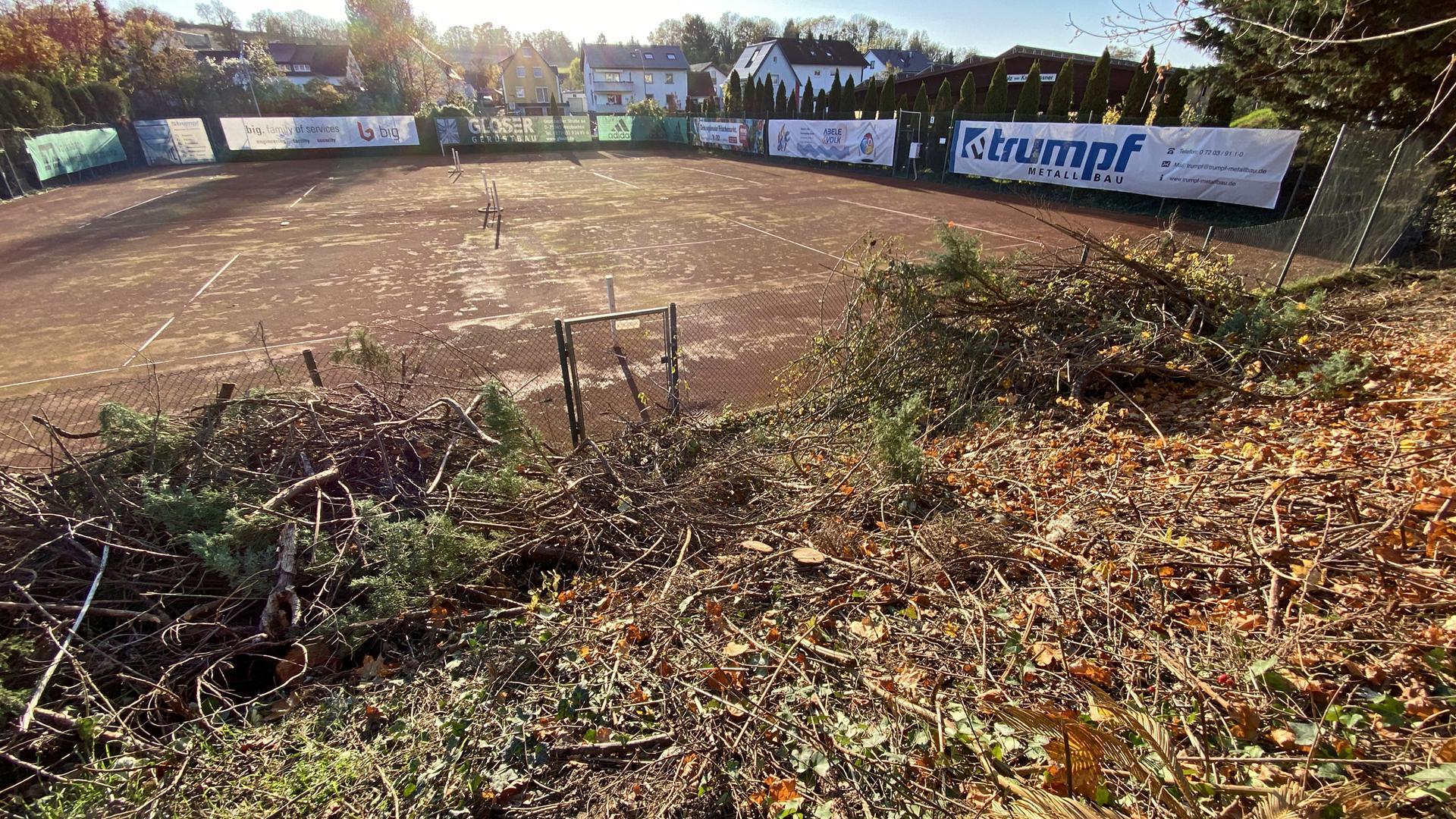 Tennisplatz, Spielflächen ohne Netze, Bandenwerbung, abgeschnittenes Grünzeug