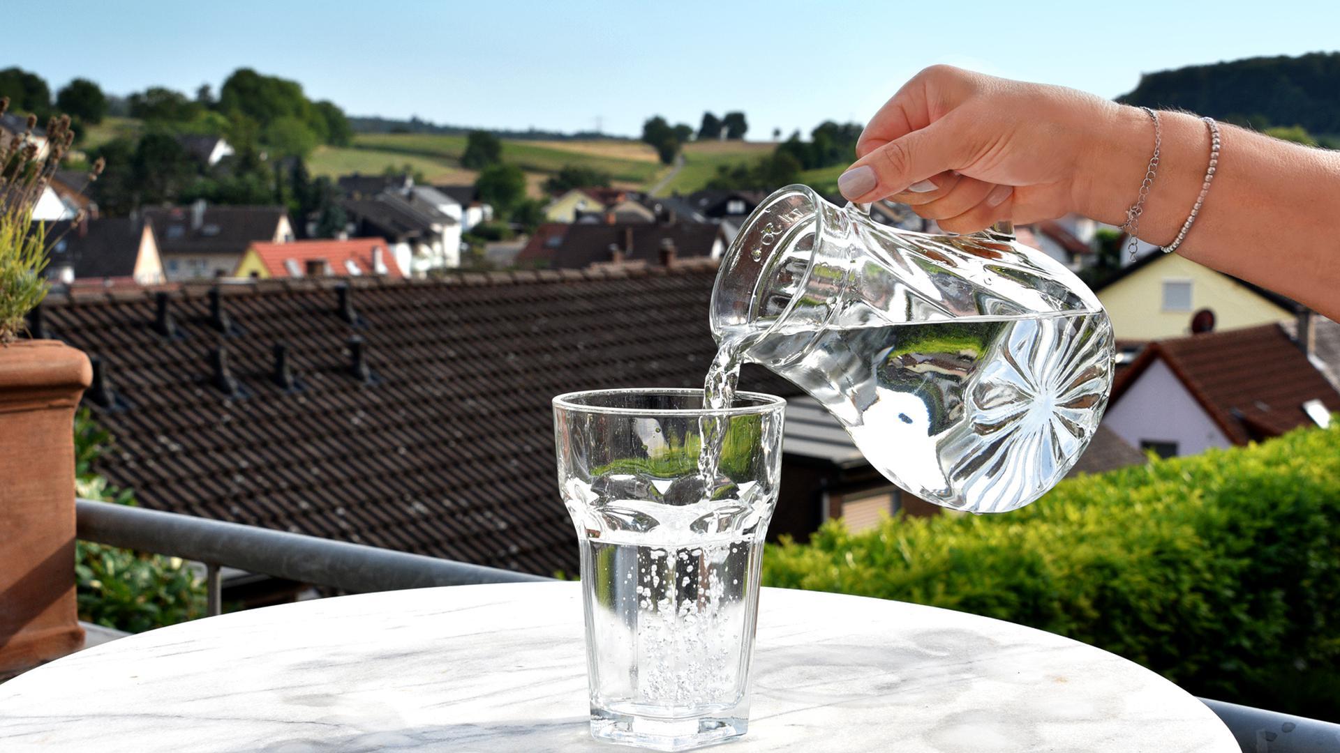 Person gießt Wasser aus einer Kanne in ein Glas.