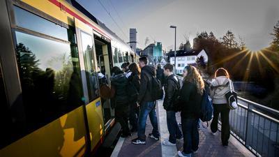 Mehrere Schüler steigen in Wössingen in die Stadtbahn. Im Hintergrund geht gerade die Sonne auf.