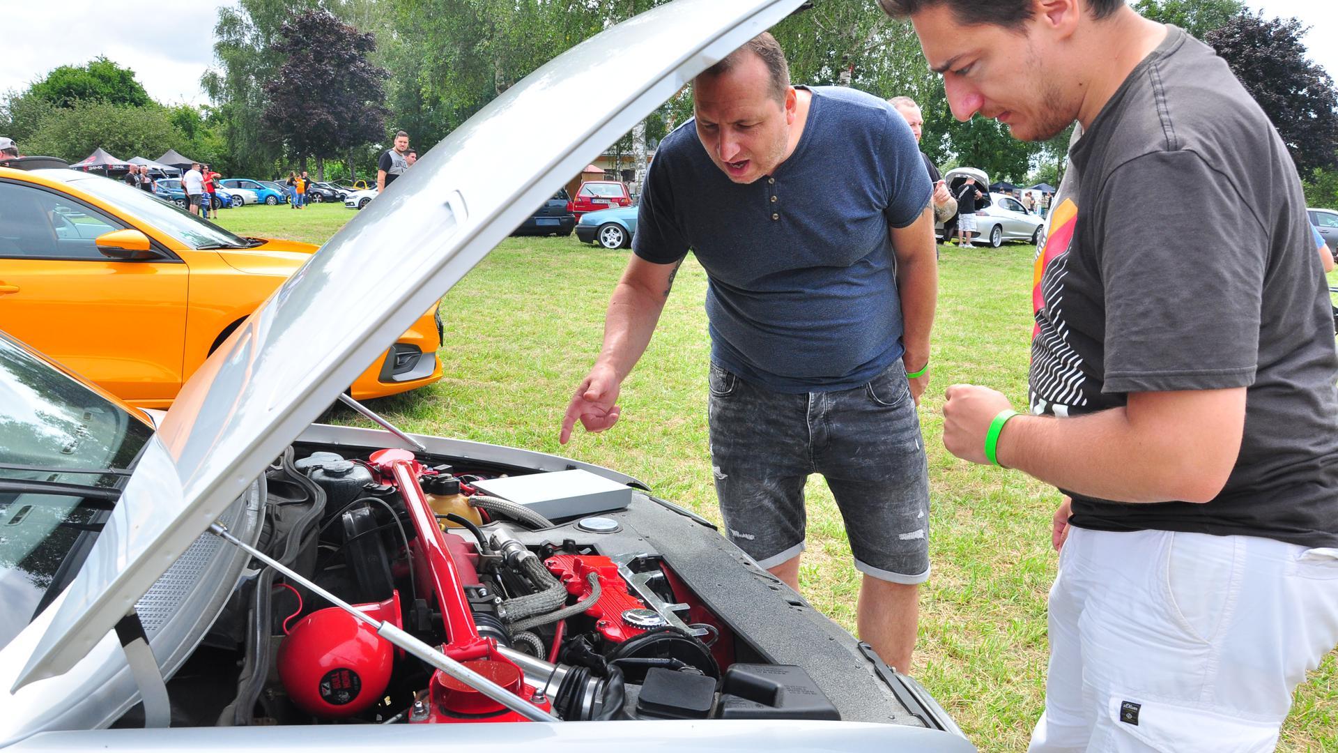 """André Kretschmer (l.) zusammen mit einem weiteren Teilnehmer von """"Eat&Chill"""" am Opel Kadett aus dem Jahr 1989. Das Treffen ist Gelegenheit, sich zu unterhalten und Erfahrungen auszutauschen."""