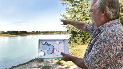 Fritz Prosi zeigt mit einer Karte vor dem Baggersee Giesen, wie groß das Gewässer angelegt ist.