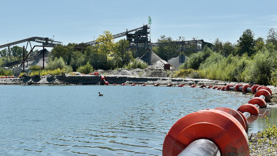 Rohre transportieren Material, das keine Verwendung findet, zurück in den See. Im Hintergrund steht das Kieswerk.