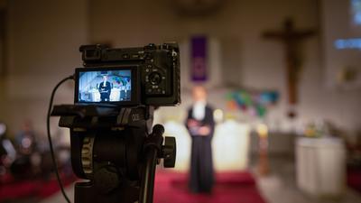 Eine Videokamera zeichnet einen Gottesdienst mit Pfarrer Simon Roth in Liedolsheim auf.