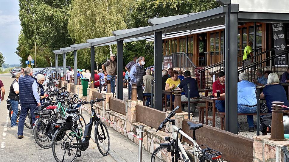 Viele Leute an Tischen und Bänken, Fahrräder, parkende Autos im Hintergrund