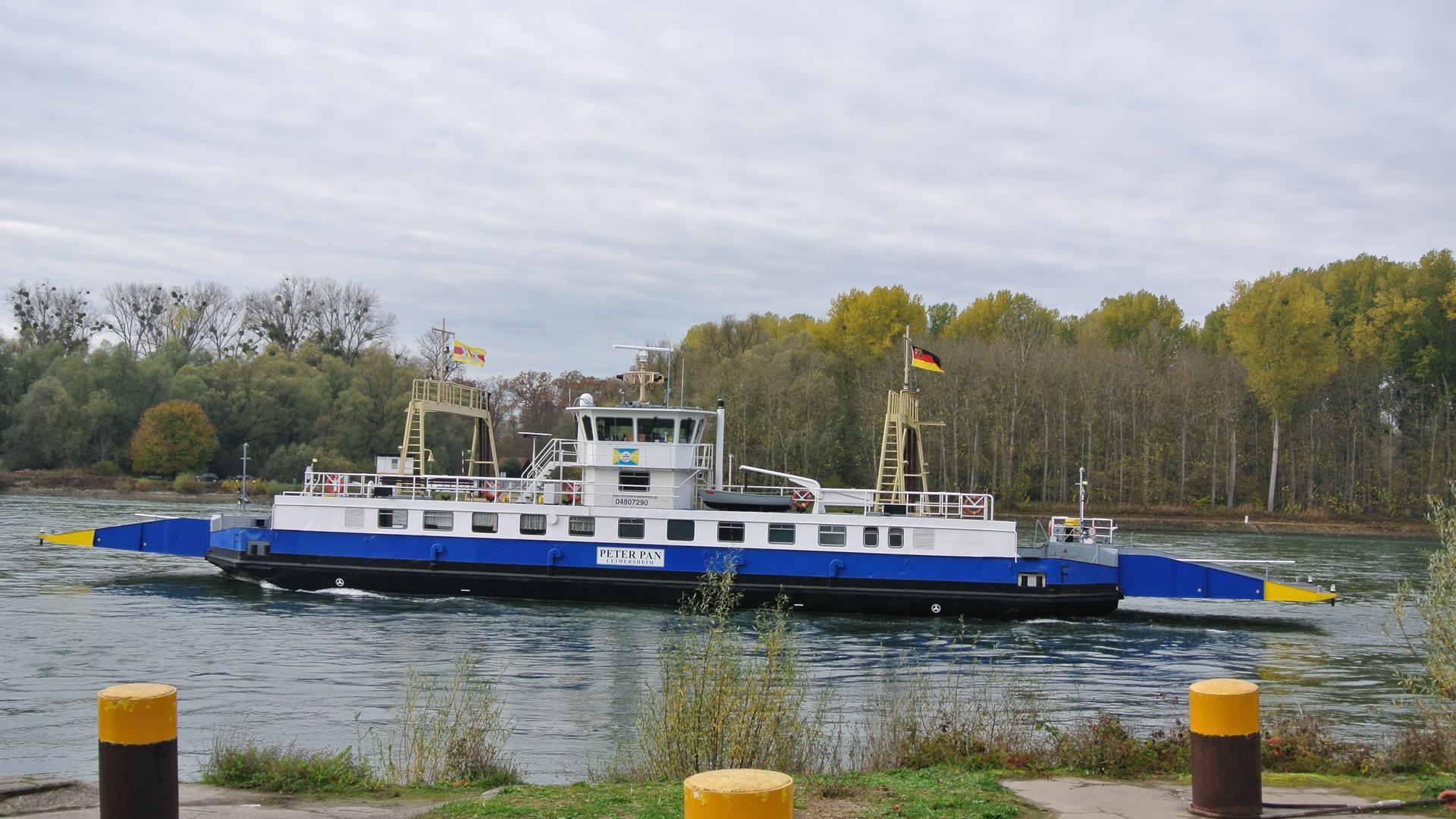 Imposanter Anblick: Die blau-weiß-gelbe Peter Pan mit der badischen und der deutschen Fahne pflügt unermüdlich durch den Rhein. Im Bild der Blick von baden-württembergischer  Seite, also von Leopoldshafen, aus.