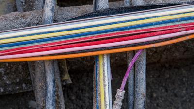 Dünne, bunte Kabel liegen quer über dickeren schwarzen