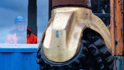 01.10.2018, Mecklenburg-Vorpommern, Schwerin: Der Bohrkopf wird bei der offiziellen Inbetriebnahme des Bohrturms zur Gewinnung von Erdwärme für die Stadt Schwerin von einem Mitarbeiter gestartet. Zukünftig sollen über das Fernwärmenetz die Schweriner Haushalte mit nachhaltiger und sauberer Wärmeenergie versorgt werden. Foto: Rainer Jensen/dpa +++ dpa-Bildfunk +++