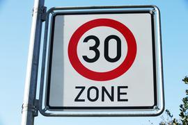 """An einer Straße steht ein """"Tempo-30""""-Schild."""