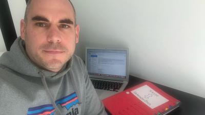 Ein Mann im Trainingsanzug vor einem Laptop