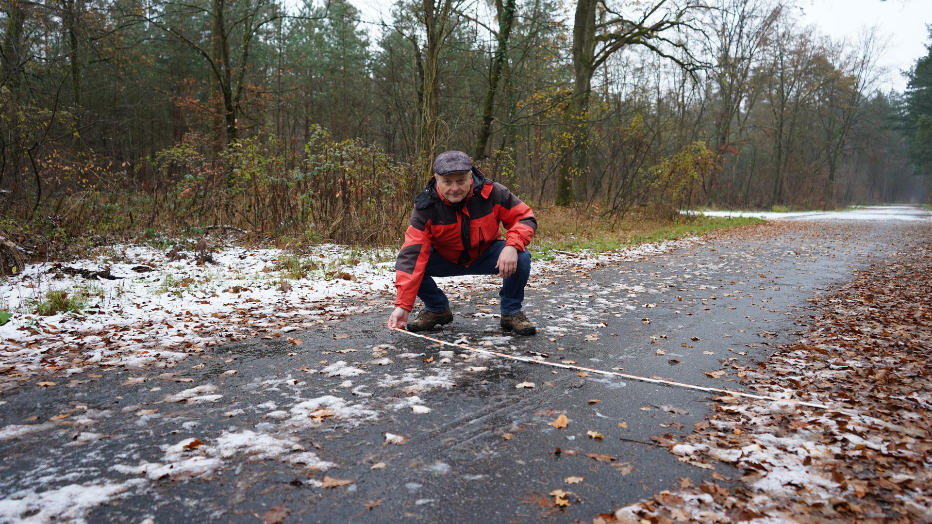 Mann mit Mütze und roter Jacke in der Hocke und misst im Wald einen Weg ab.