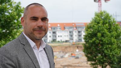 """Bürgermeister Christian Eheim mit der """"Neuen Mitte"""" – gegenüber vom Graben-Neudorfer Rathaus – im Hintergrund."""