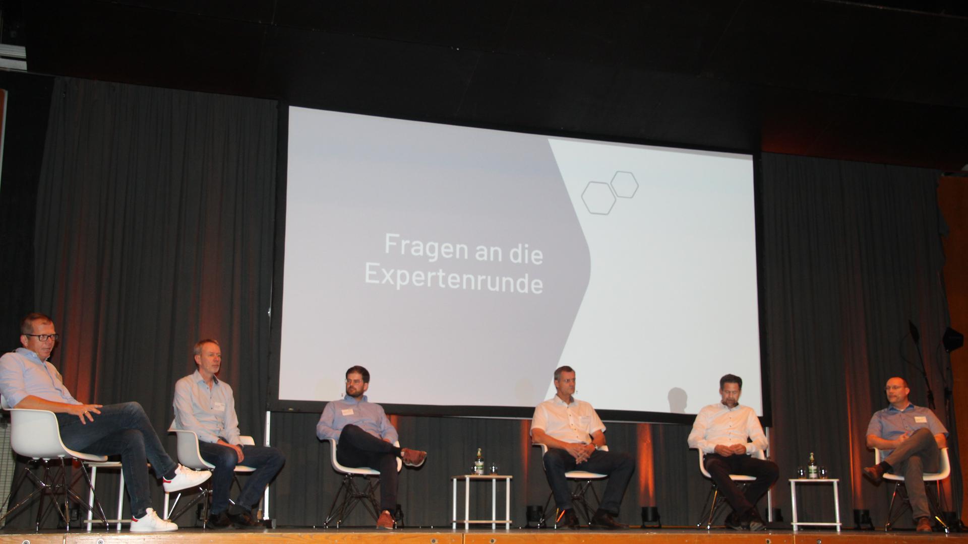 Im Stuhlhalbkreis auf einer Bühne sitzend Experten beim Geothermie-Infotag in Graben-Neudorf