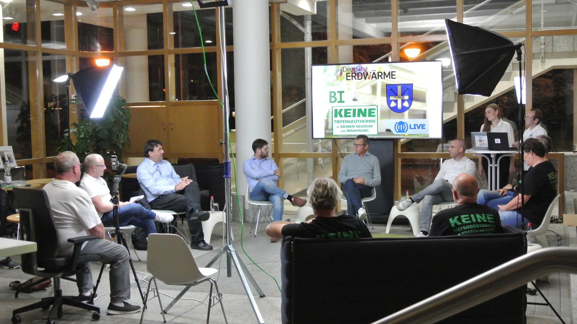 Diskussionsrunde von 9 Personen zu Erdwärme in Graben-Neudorf. Hinter der Runde Licht- und Tontechnik