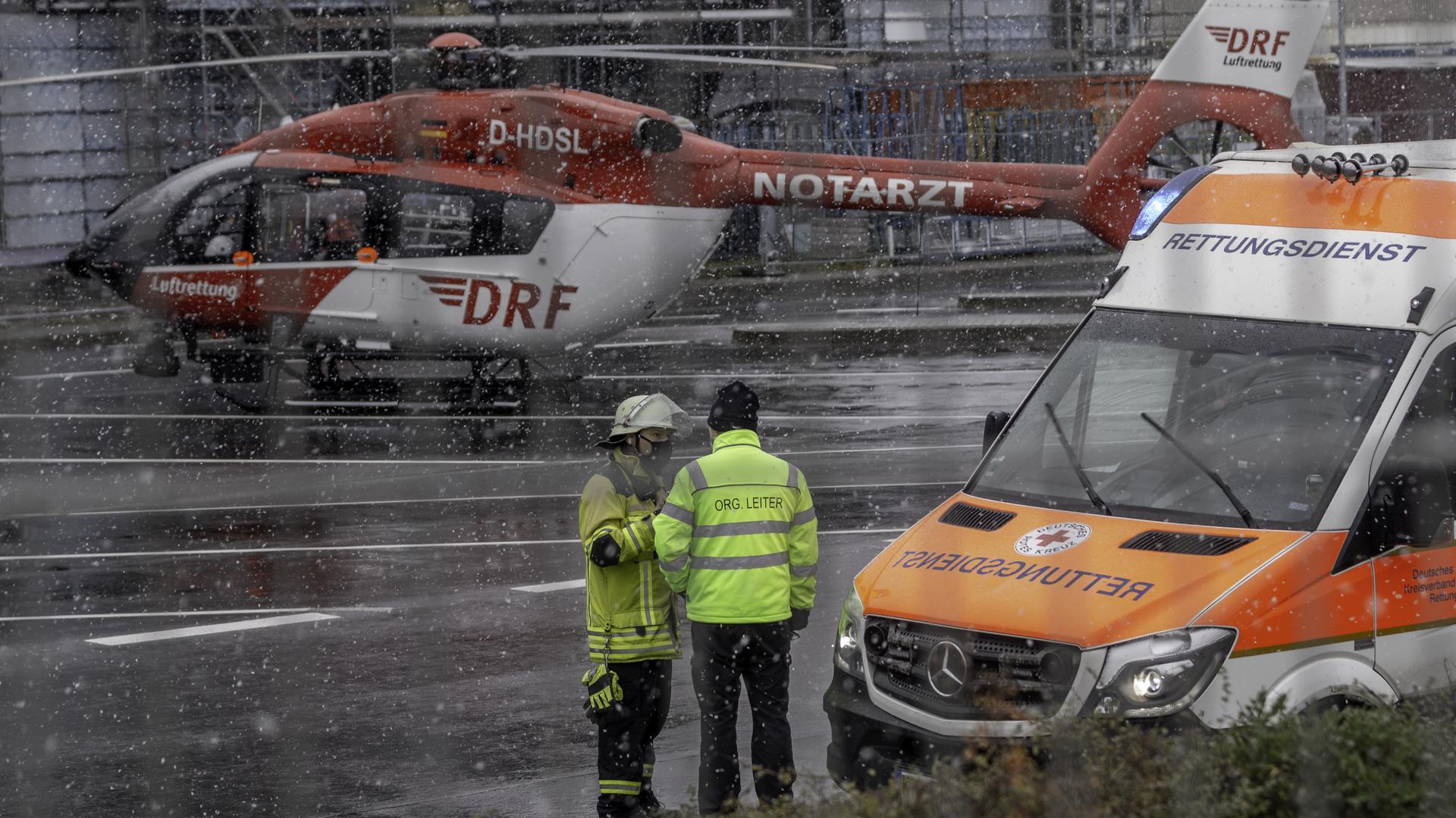 Ein Rettungshubschrauber und ein Rettungsfahrzeug stehen auf einem Werksgelände