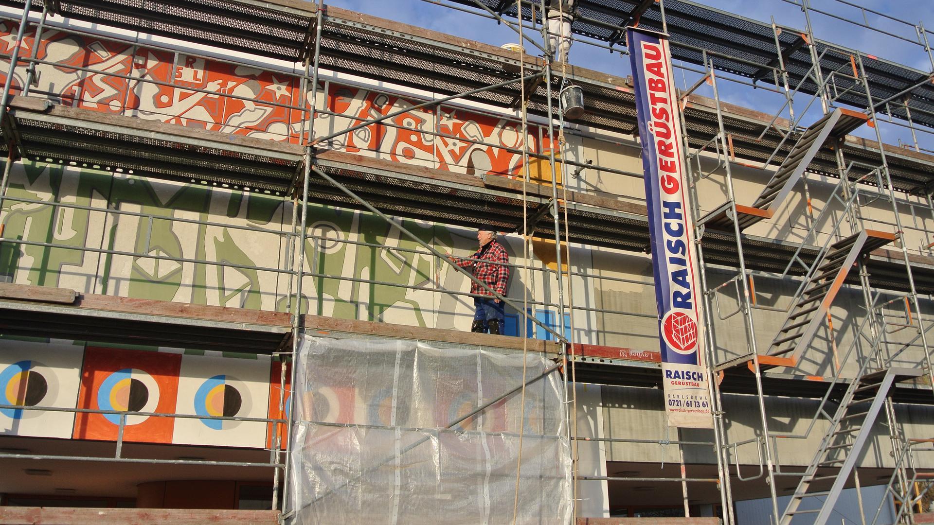 Auf einem Gerüst steht ein Mann an einer Außenfassade eines Hauses und malt