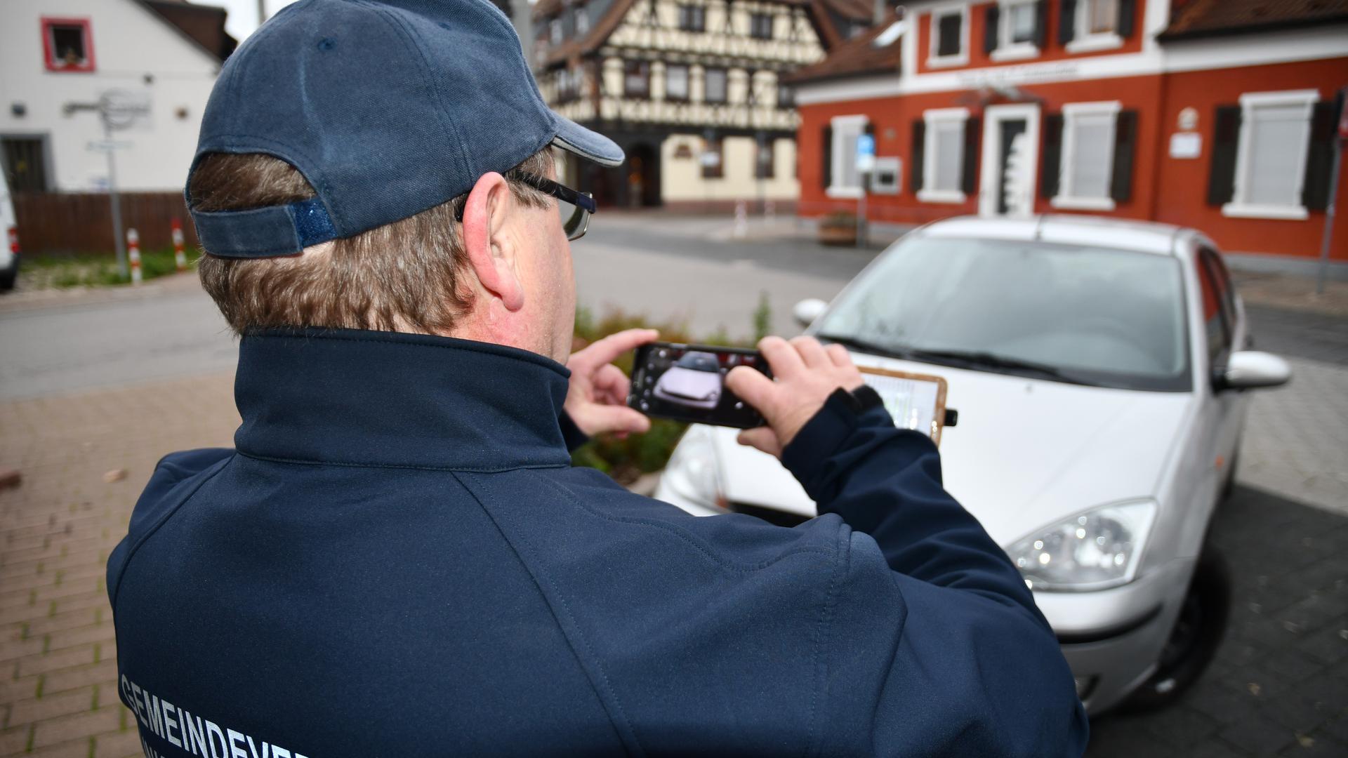 Burkhard Stengl steht mit dem Rücken zum Leser. Mit seinem Handy schießt er Fotos von einem falsch geparkten silbernen Auto.