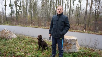 Mann mit einem Hund lehnt an einem großen Stein am Wegrand.