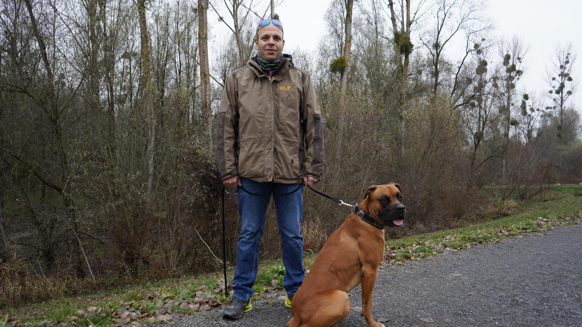 Mann mit Sonnenbrille und Jacke, auf einem Damm mit einem Hund an der Leine.