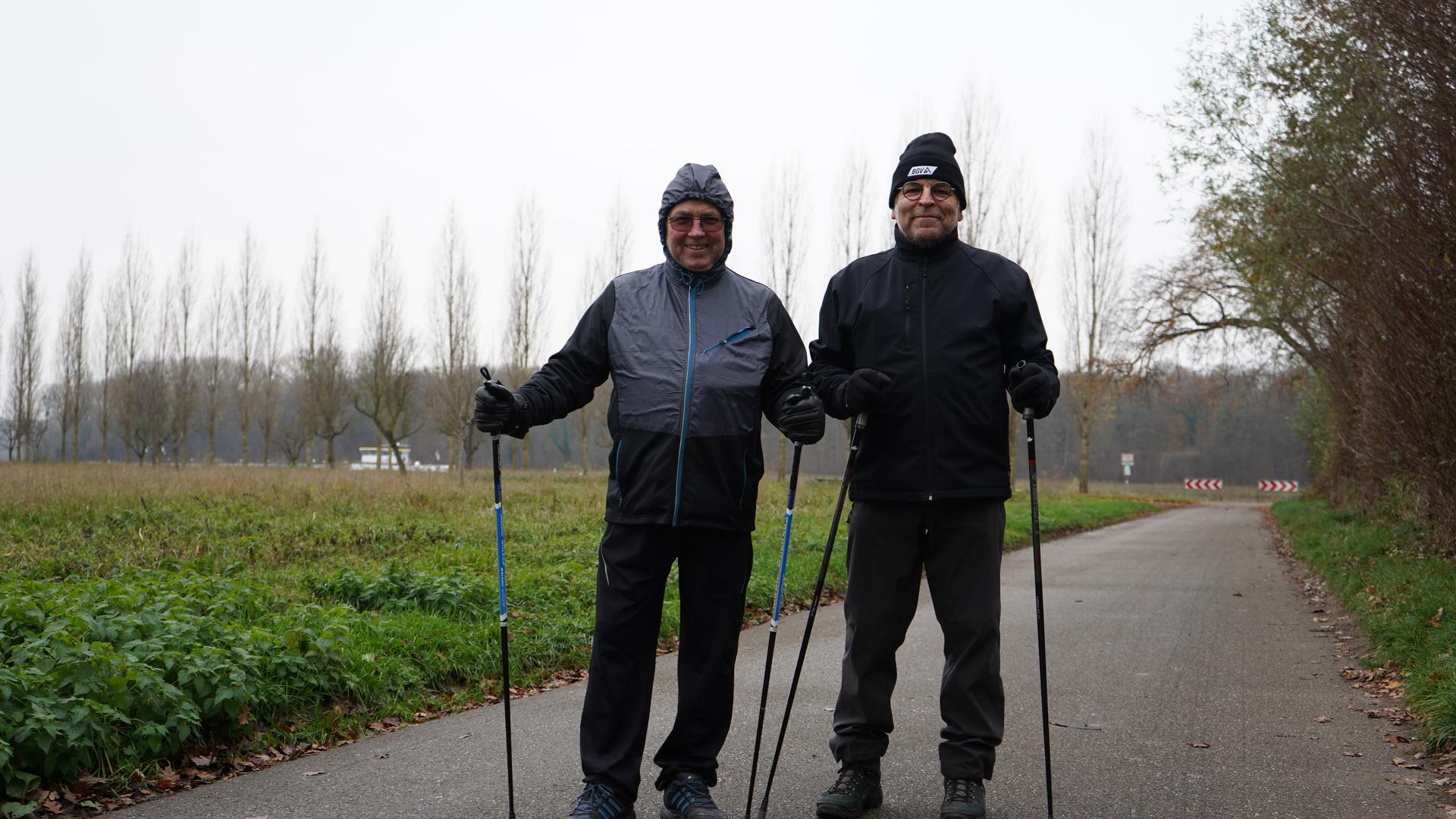 Zwei Männer auf der Straße mit Nordic-Walking-Stöcken