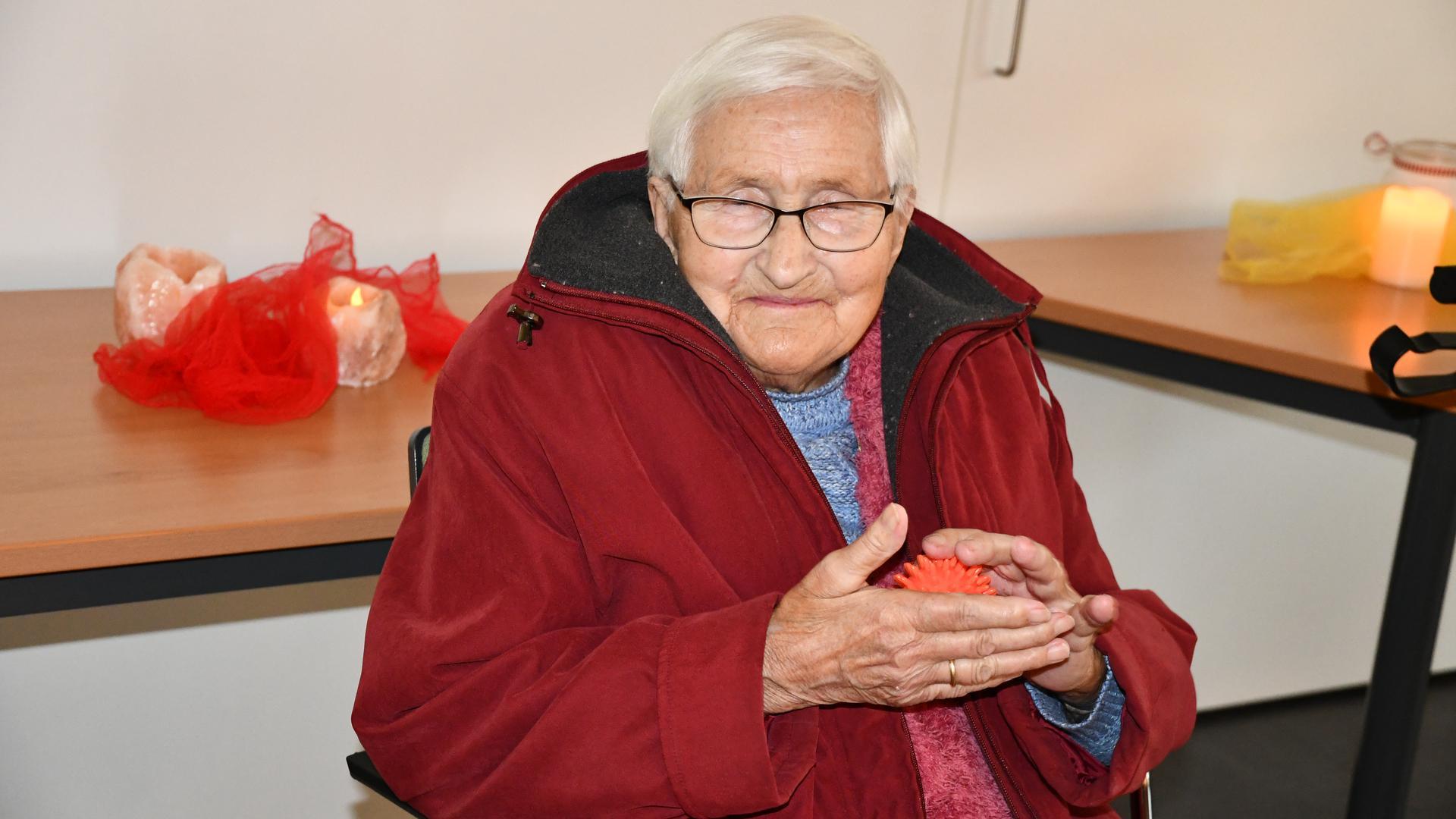 Die 90-jährige Gerda Seith sitzt auf einem Stuhl und rollt einen Noppenball in den Händen.