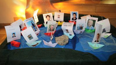 Fotos von Kommunionskindern mit Papierschiffen und Kerzen