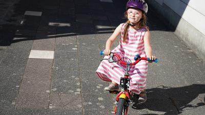 Mädchen mit Helm und Kinderfahrrad.