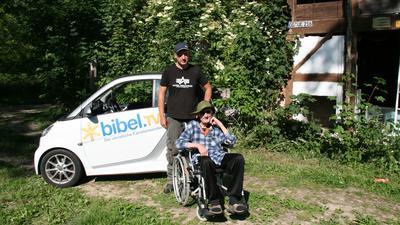 Olaf Stuckas sitzt im Rollstuhl auf einer Wiese. Marcel Kulz steht hinter ihm.