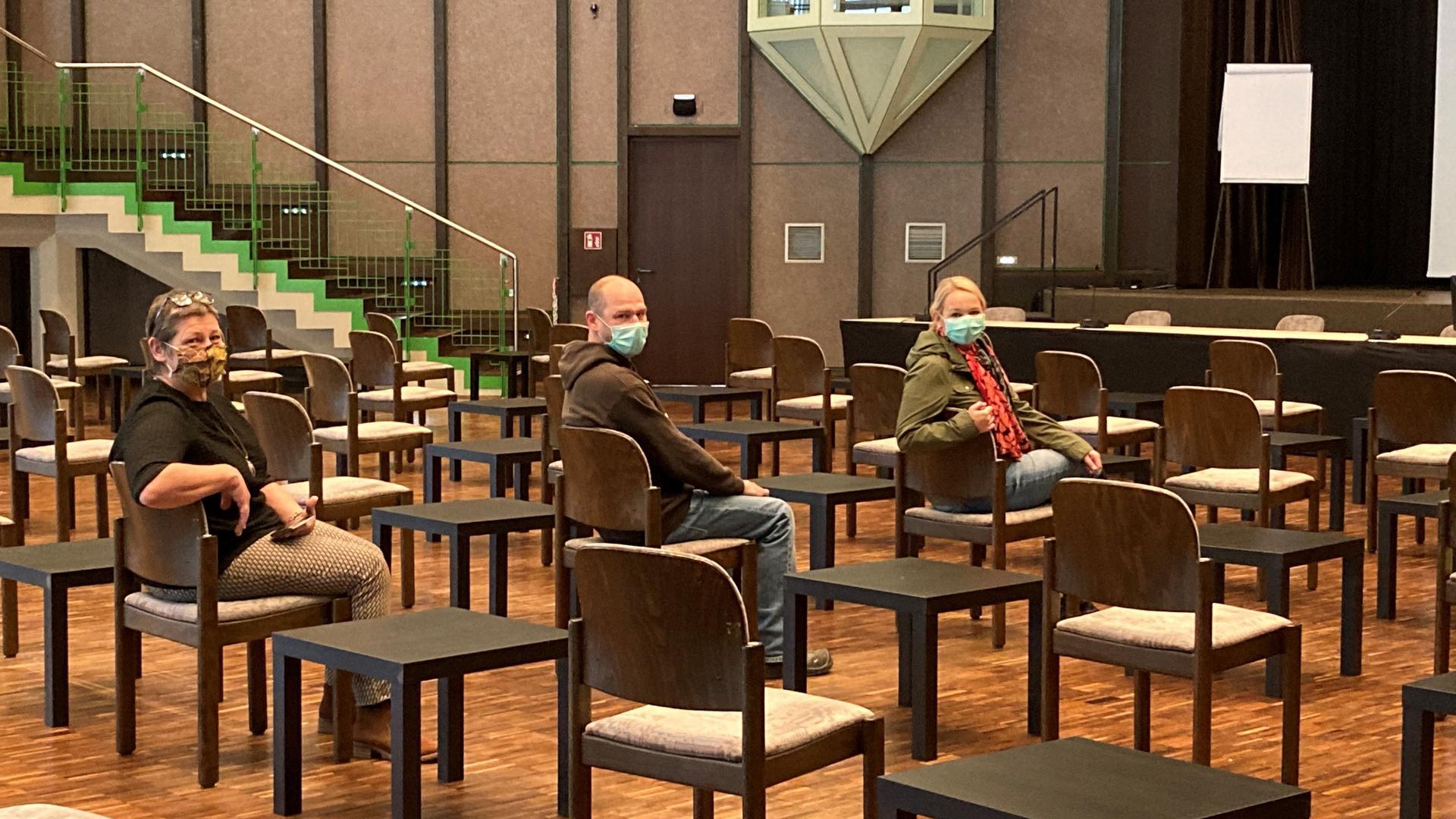 Drei Leute in Saal