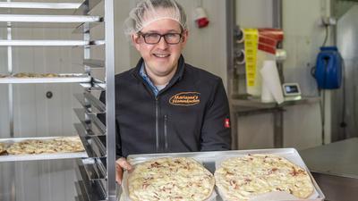 """Christian Pudlo von """"Marianne's Flammkuchen"""" steht in seiner Produktionshalle und zeigt zwei Flammkuchen."""