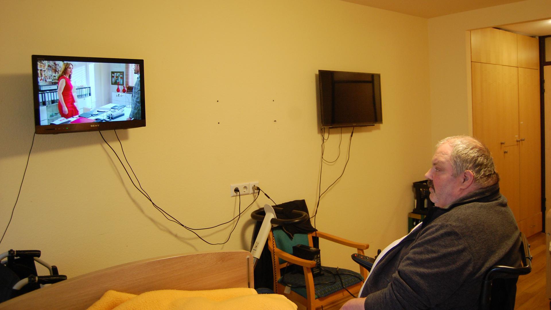 Uwe Bonrath sitzt in seinem Rollstuhl und guckt in einen Fernseher.