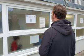 Mann liest Corona-Vorschriften an Hallenfenster der Fußballvereinigung Weingarten