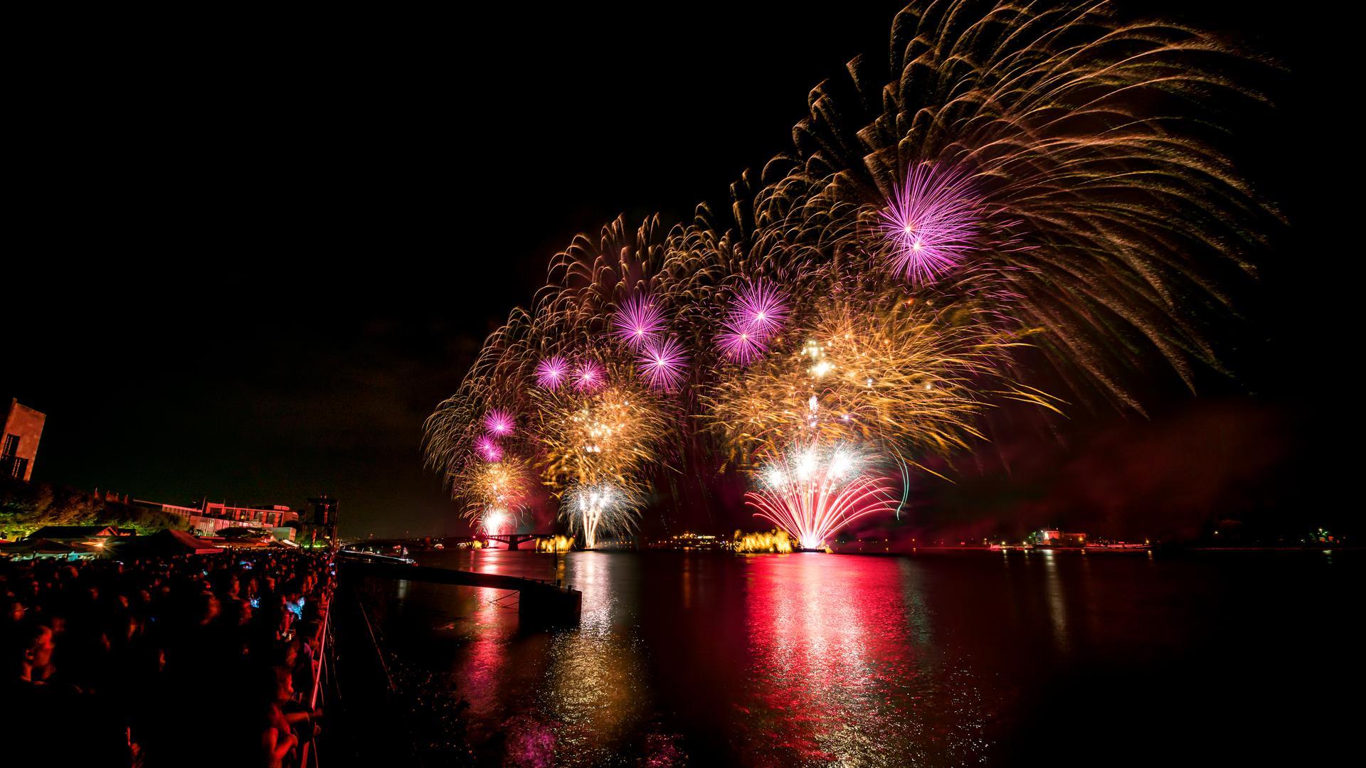 Menschen am Ufer des Rheins schauen bei Nacht auf ein spektakuläres Feuerwerk.