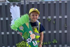Jan trägt eine große grüne Schultüte mit Fußball-Motiv.