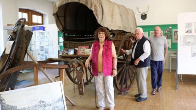 Drei Personen an Planwagen stehend, der ausgestellt in einem Innenraum steht