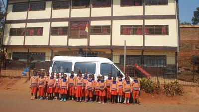 Kinderschar in Kamerun vor Spendenbus stehend der vor Gebäude parkt