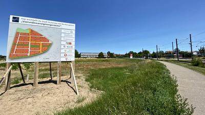 Großes Schild mit Plan, Grundstück, Schulgebäude im Hintergrund, Straßenbahnlinie