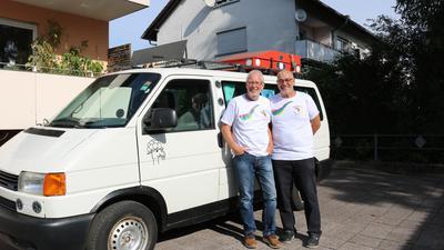 Zwei Männer stehen neben Mini-Van