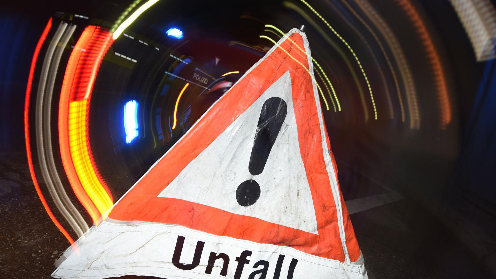 """Ein Warndreieck mit dem Schriftzug """"Unfall"""" steht auf einer Straße."""