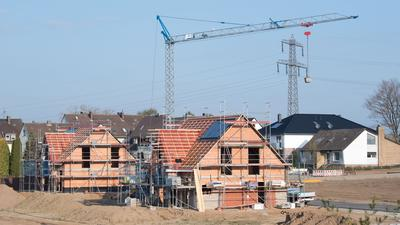 Einfamilienhäuser stehen im Rohbau in einem Neubaugebiet