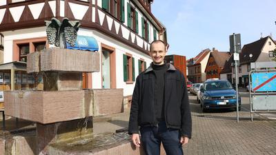 männliche Person neben Dorfbrunnen