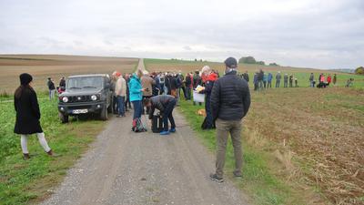 Eine Gruppe von Menschen versammelt sich auf einem Feld.