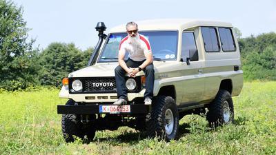 Offroader auf der Motorhaube seines Fahrzeugs sitzend.